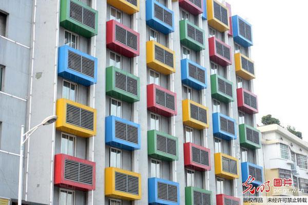 """2015年8月11日,湖南郴州,市民、车辆从""""多彩空调楼""""下经过。当日,湖南郴州现""""多彩空调楼""""。某房子外墙悬挂30余个巨大彩色空调罩,显得新颖、个性。"""