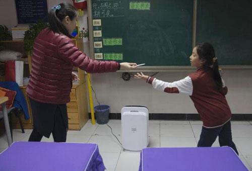 12月8日,北京市海淀外国语实验学校的教室里开启了空气净化器。