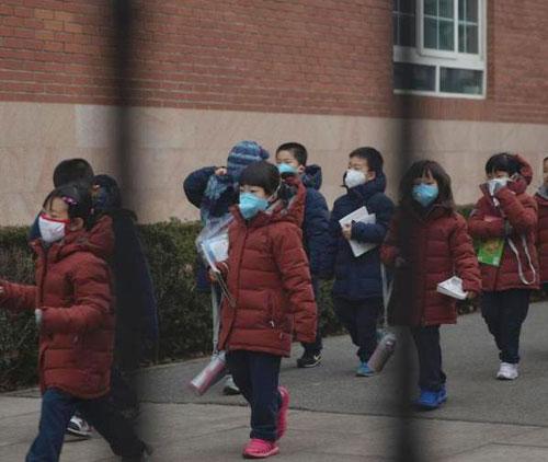 北京市海淀外国语实验学校的学生在教师的带领下前往室内活动。