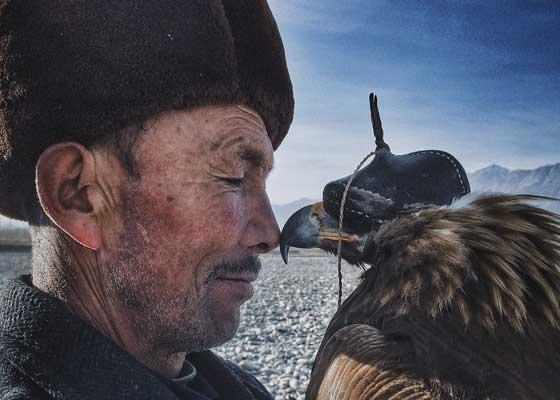 """中国业余摄影师牛思远获得2016年第九届iPhone摄影大赛年度摄影师大奖,他的作品为""""人与鹰""""。"""
