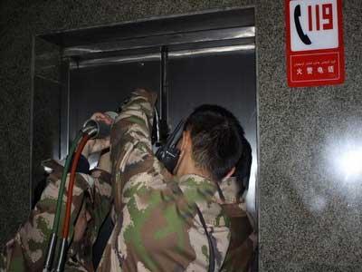 厦门:男子被困电梯 消防破墙救人
